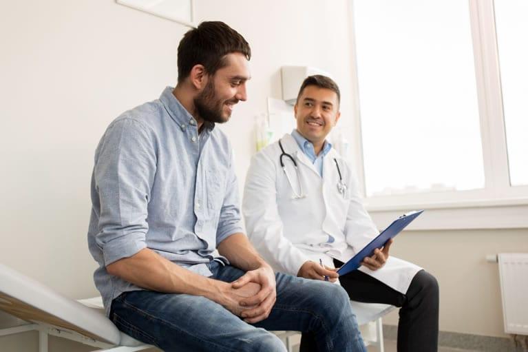 Médico descrevendo o resultado de uma tomografia com contraste para o paciente sentados na maca