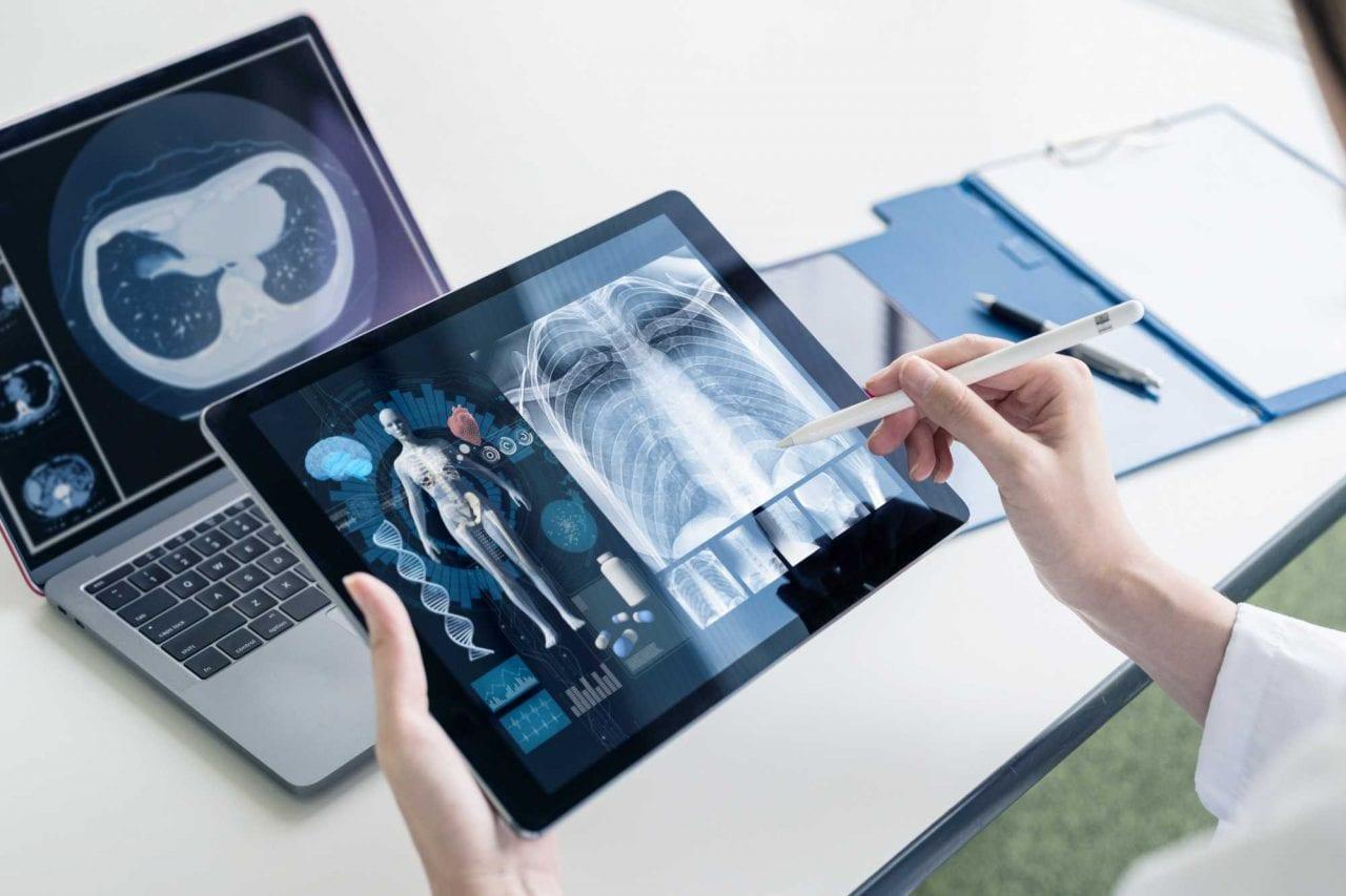 Médico fazendo telediagnóstico em vários dispositivos