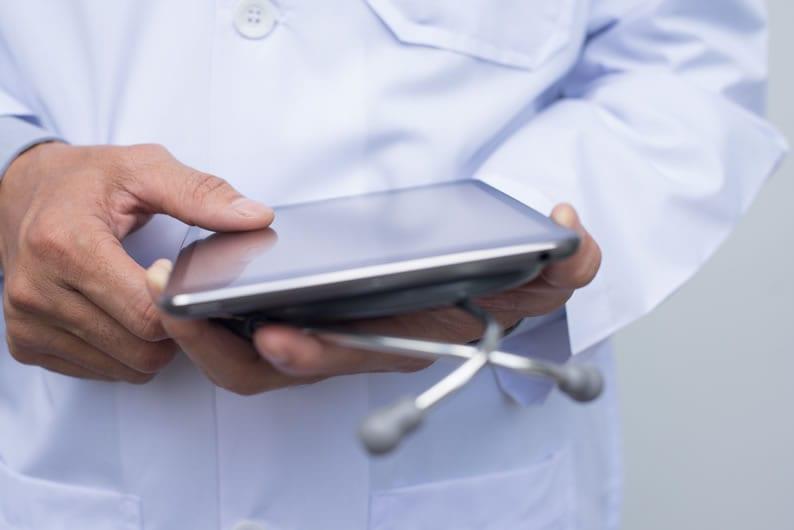 Médico com tablet na mão interpretando exames
