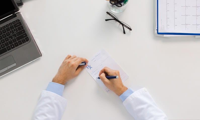 Médico prescrevendo uma receita para o colaborador