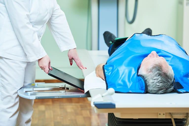 Técnico posicionando o paciente para realizar rx de abdome