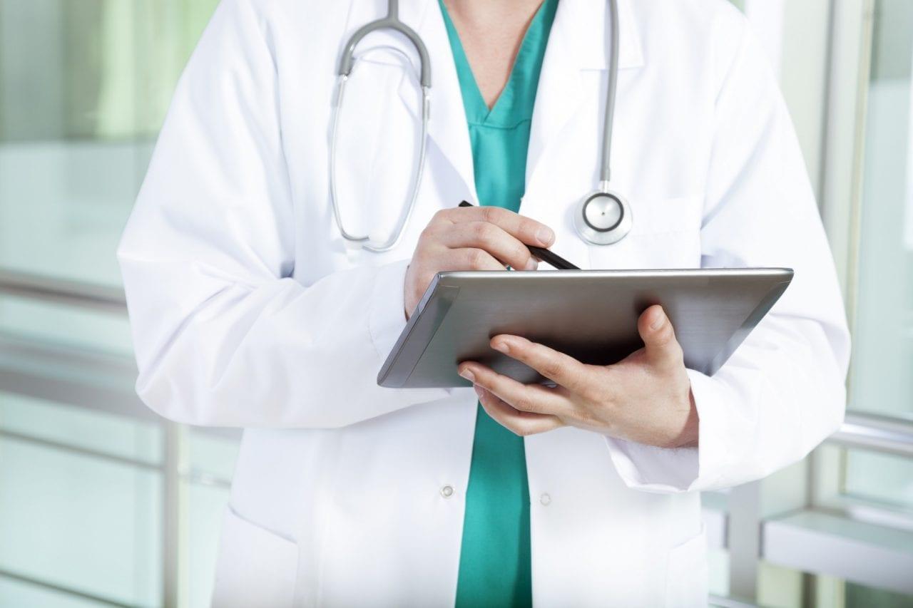 Médico segurando um tablet com bulário online